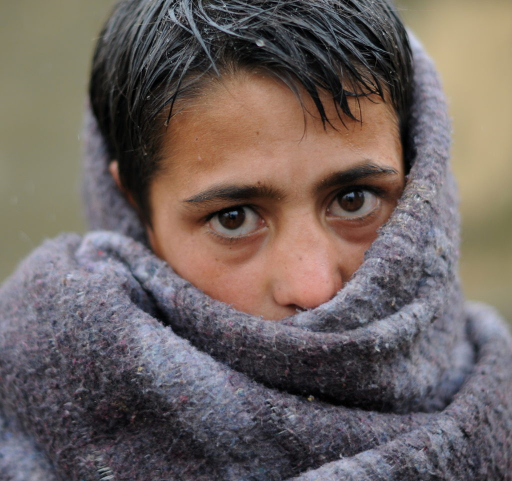 Teenage refugee boy wrapped in a blanket